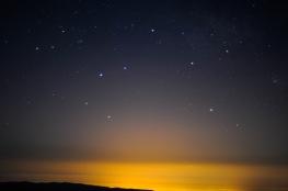 Fulgor no horizonte con estrelas por enriba.